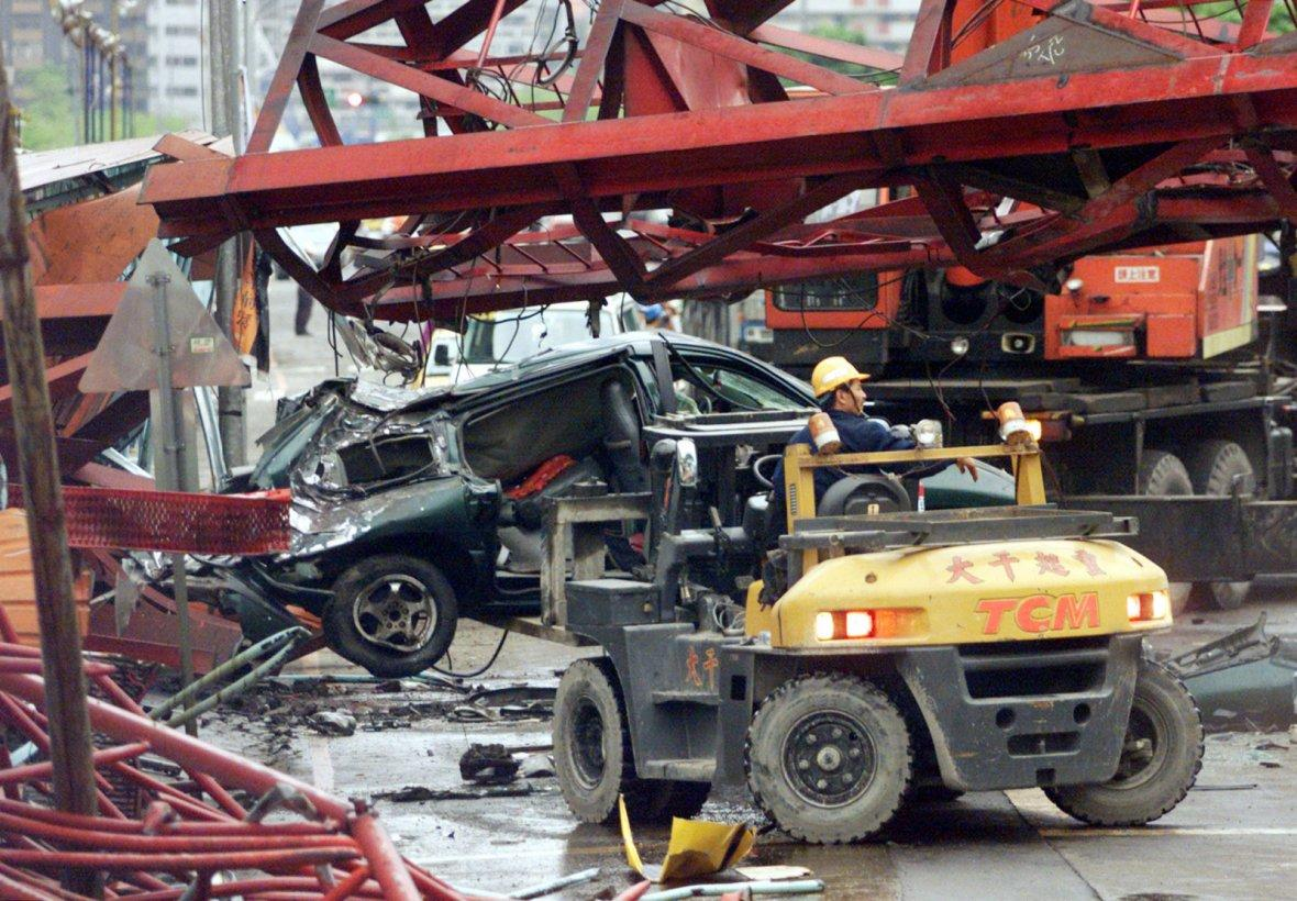 Rescue workers remove a crashed car from a collapsed construction crane in Taipei.