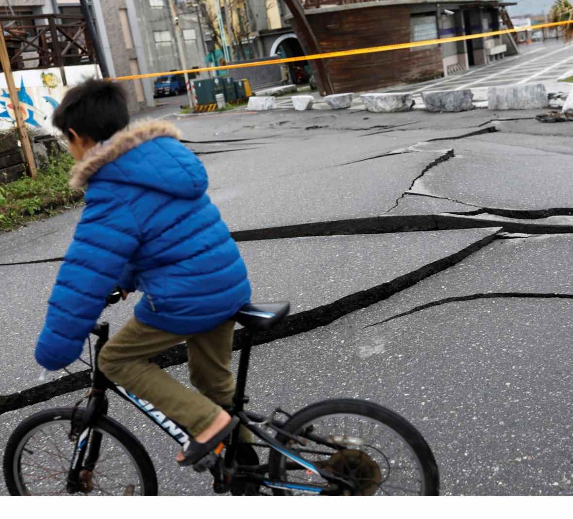 A child rides a bicycle on a fractured road after an earthquake hit Hualien