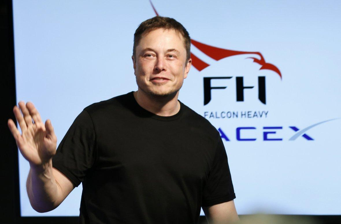 SpaceX founder Elon Musk waves at a press conference following the first launch of a SpaceX Falcon Heavy rocket at the Kennedy Space Center