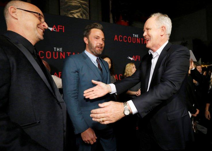 "Director O'Connor greets cast members Affleck and Lithgow at the premiere of ""The Accountant"""