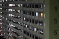Residents and people crowd the corridors of a public housing estate