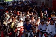 Malaysian motorcyclists wait to go through customs at the Malaysia - Singapore border