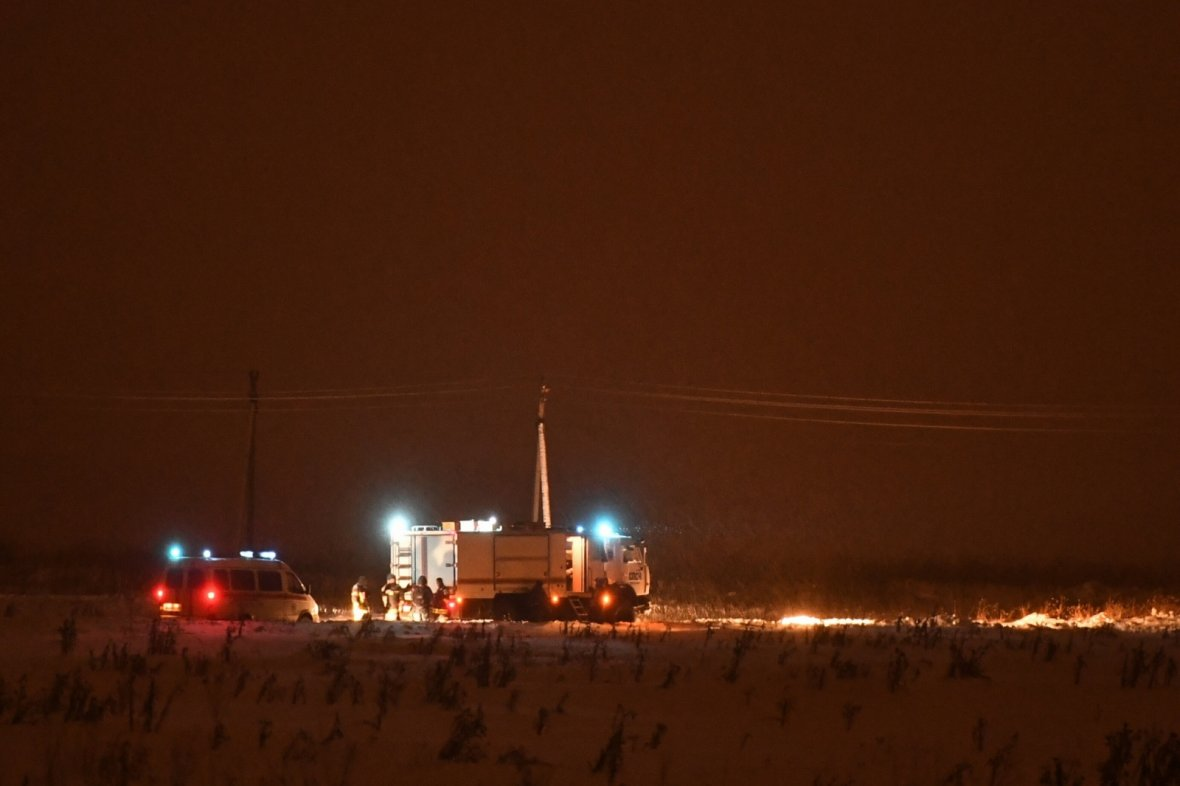 Russian Emergencies Ministry employees work near the site of an air crash outside Moscow