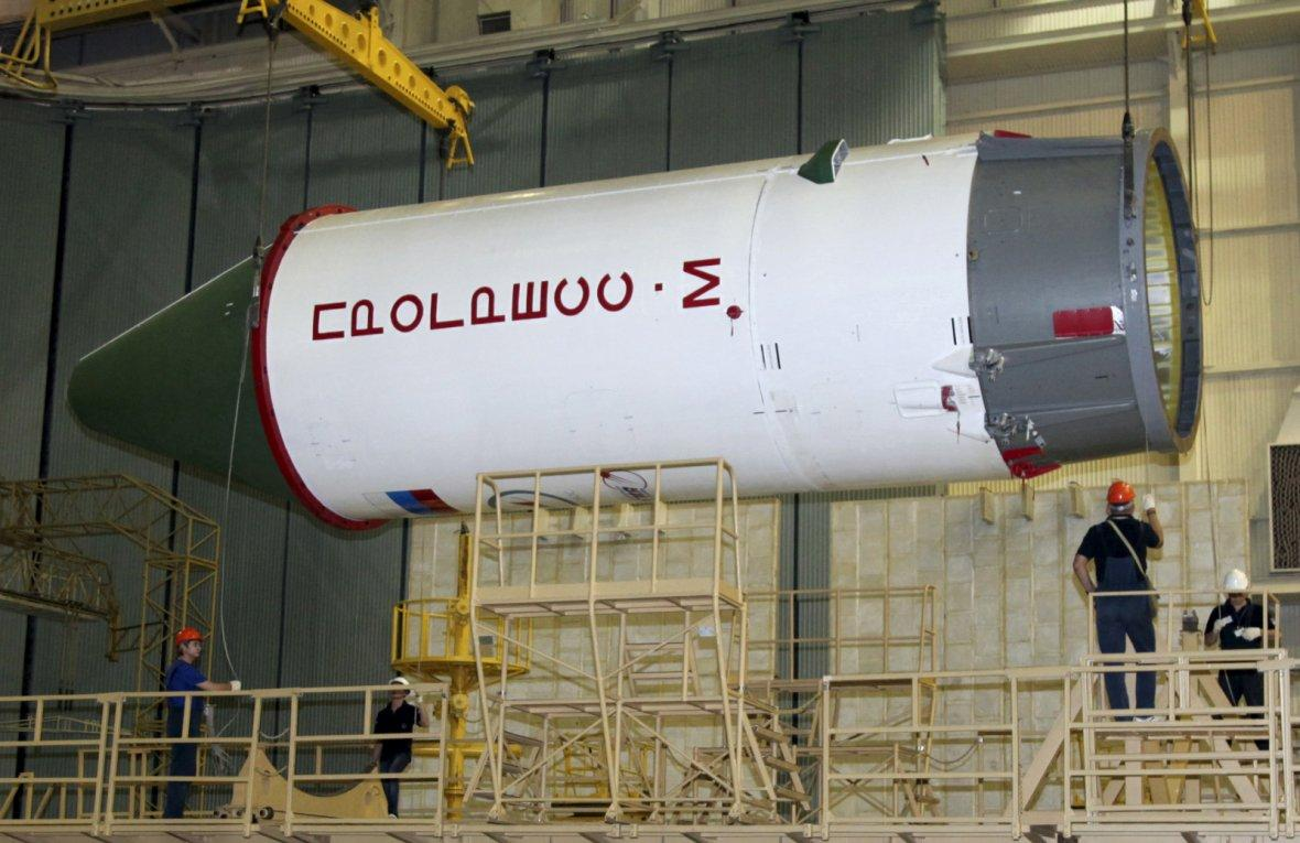 Employees work on a Russian Progress-M spacecraft during the preparations for the upcoming launch