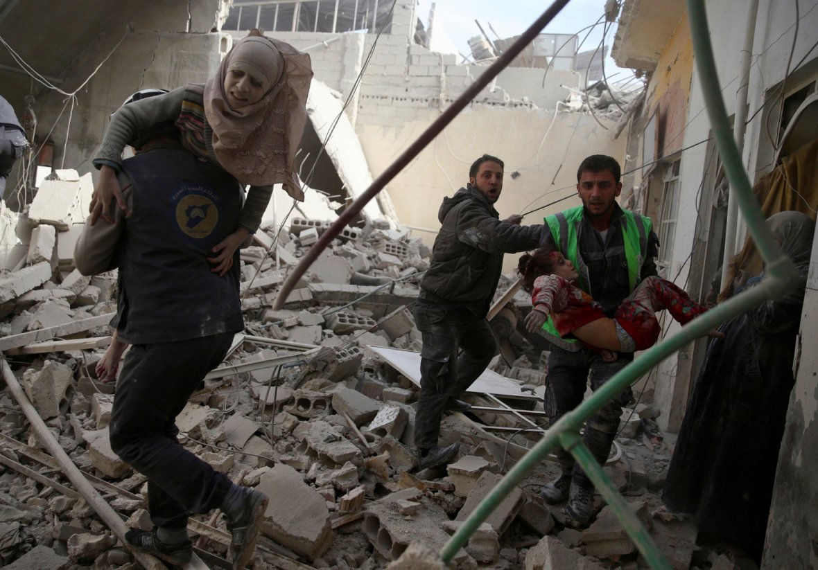 Civil defence members carry injured girls after an airstrike in the rebel-held Douma neighbourhood of Damascus, Syria