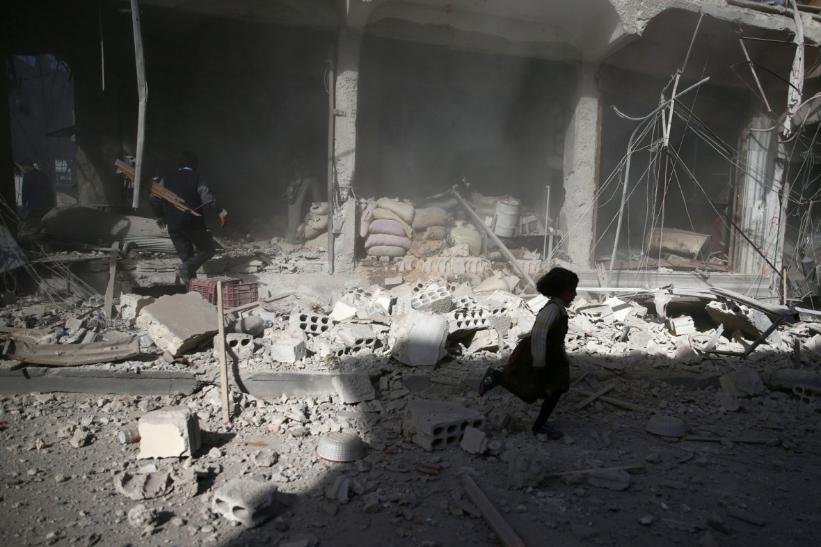 A girl runs past a damaged site after an airstrike in the besieged rebel-held town of Douma, eastern Ghouta in Damascus, Syria