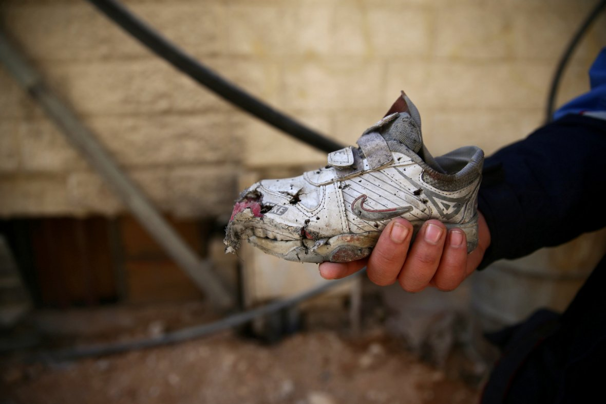 A man shows a damaged shoe of a child, after an air strike on a kindergarten in the rebel-held besieged city of Harasta, in the eastern Damascus suburb of Ghouta, Syria