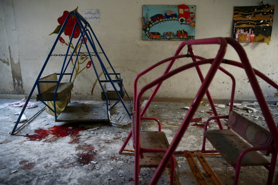 Blood stains the ground under swings in a damaged kindergarten after an air strike in the rebel-held besieged city of Harasta, in the eastern Damascus suburb of Ghouta, Syria