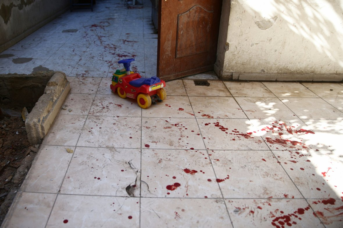 A toy vehicle lies next to blood stains on the ground of a kindergarten after an air strike in the rebel-held besieged city of Harasta, in the eastern Damascus suburb of Ghouta, Syria