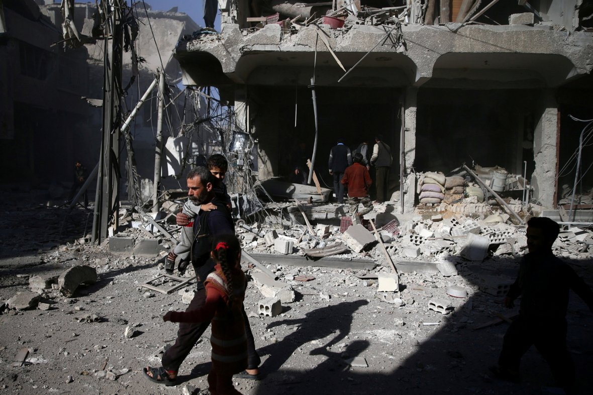 A man carries a boy past a damaged site after an airstrike in the besieged rebel-held town of Douma, eastern Ghouta in Damascus, Syria