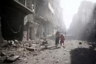 People walk past a damaged site after an airstrike in the besieged rebel-held town of Douma, eastern Ghouta in Damascus, Syria