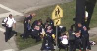 Rescue workers deal with a victim near Marjory Stoneman Douglas High School during a shooting incident in Parkland, Florida
