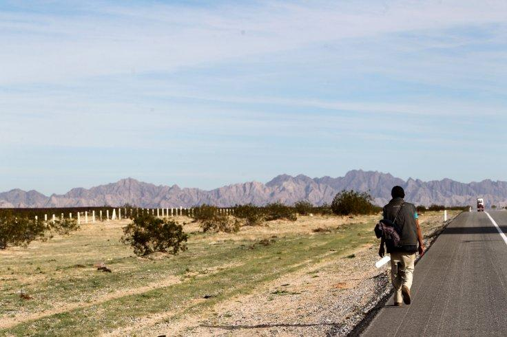 A migrant walks on a highway in the Mexican state of Sonora