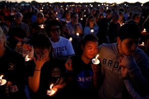 People attend a candlelight vigil for victims of the shooting at nearby Marjory Stoneman Douglas High School, in Parkland, Florida