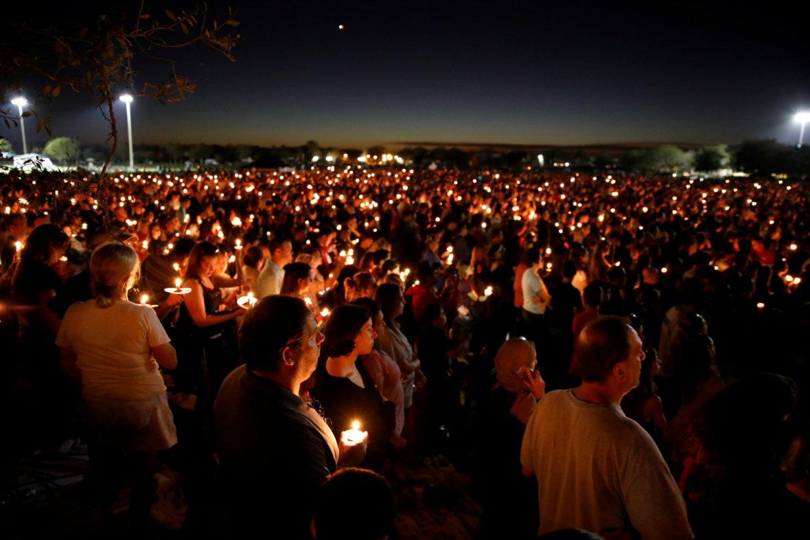 People attend a candlelight vigil for victims of the shooting at nearby Marjory Stoneman Douglas High School