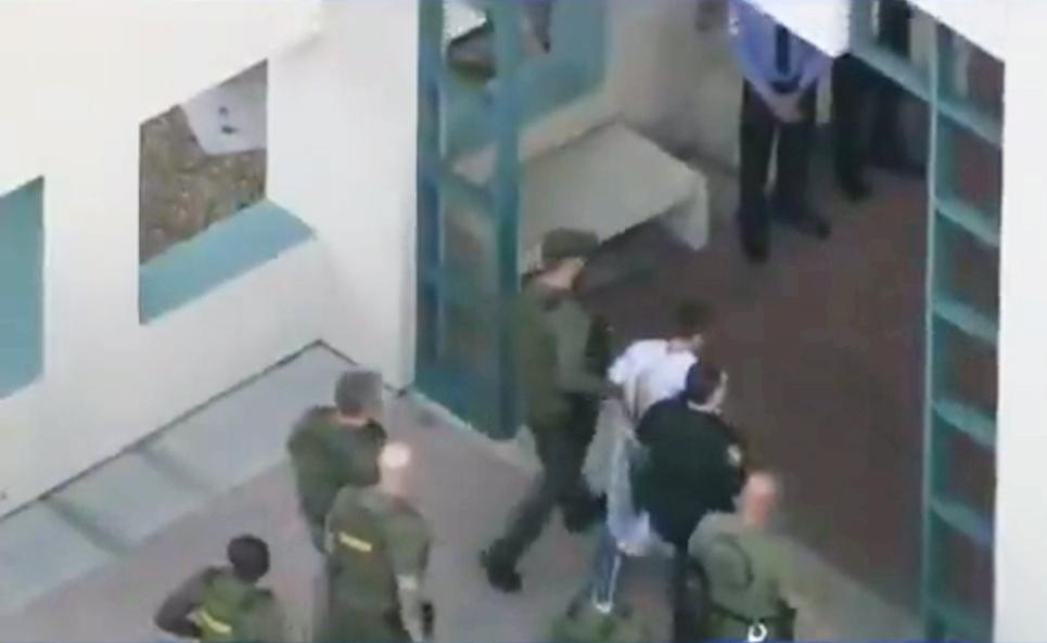 Police escort a suspect into the Broward Jail after checking him at the hospital following a shooting