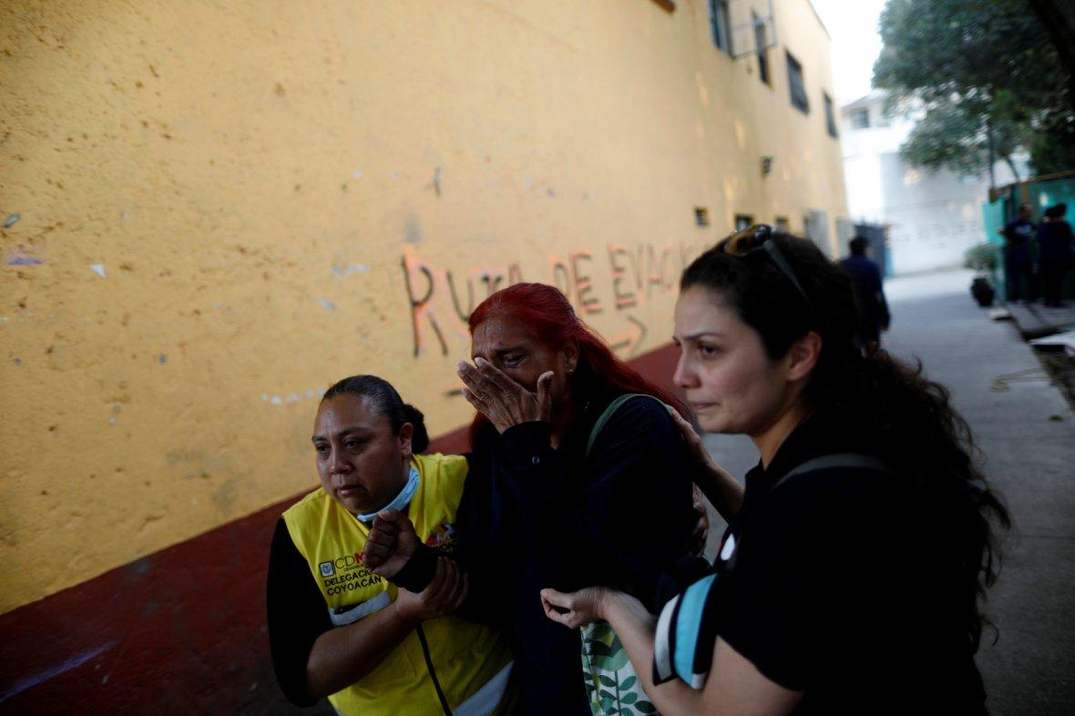 People react after an earthquake shook buildings in Mexico City, Mexico