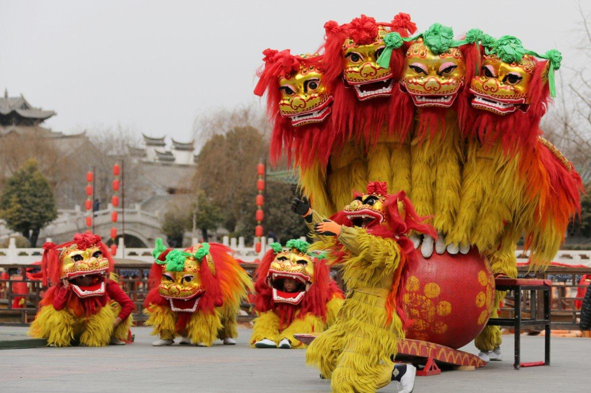 Folk artists perform a lion dance ahead of the Chinese Lunar New Year, or Spring festival, at Taierzhuang Ancient Town scenic area in Zaozhuang