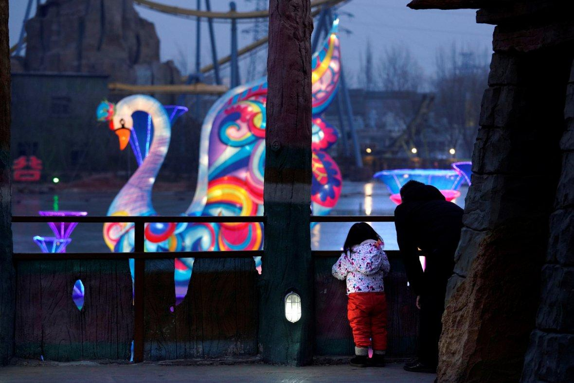 A man and his daughter watch a light show to celebrate Chinese Lunar New Year of the Dog at Happy Valley in Beijing