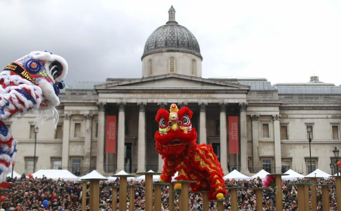 Spectators watch performers dressed in traditional lion and dragon costumes take part in the Chinese New Year parade