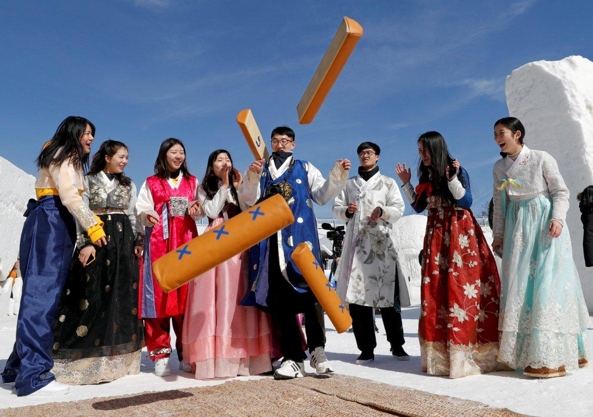 People dressed in traditional Korean clothes play a game as they celebrate Lunar New Year among ice sculptures in Pyeongchang