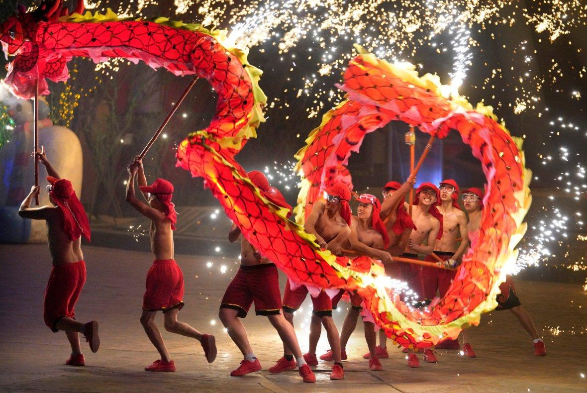 Folk artists perform a fire dragon dance under a shower of sparks from molten iron during a traditional performance to celebrate Chinese Lunar New Year