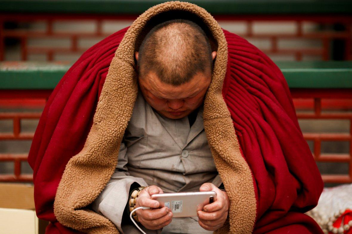 A man uses a smart phone at a Buddhist temple in Badachu park during Spring Festival celebrations marking Chinese New Year