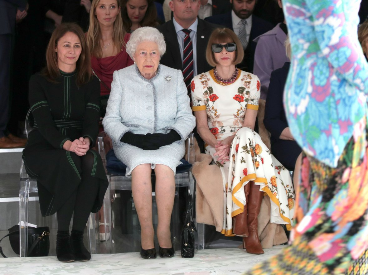 Britain's Queen Elizabeth II sits next to Vogue Editor-in-Chief Anna Wintour and Caroline Rush