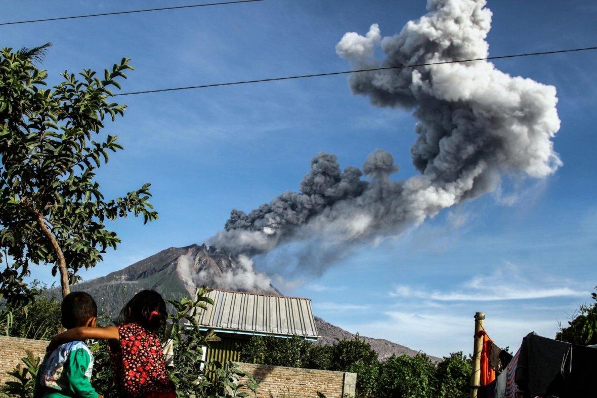 Children watch as Mount Sinabung volcano spews smoke and ash in Karo, North Sumatra of Indonesia