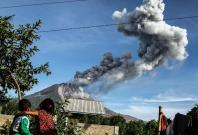 Children watch as Mount Sinabung volcano spews smoke and ash in Karo, North Sumatra of Indonesia