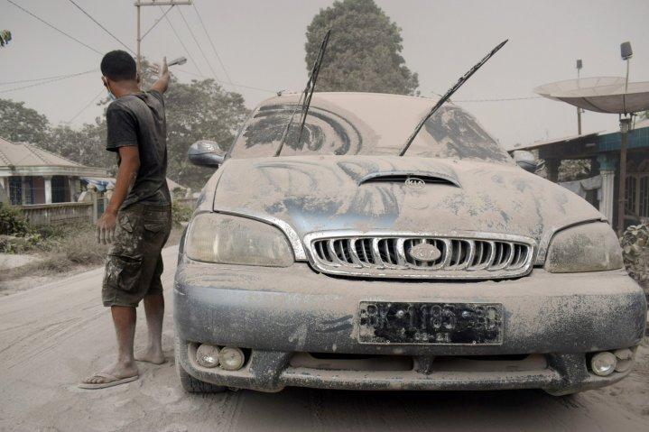 Ash from Mount Sinabung volcano covers a car and street following an eruption in Karo