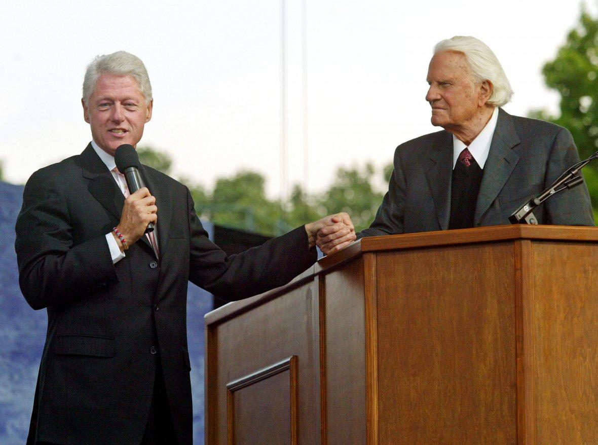 Former president Bill Clinton clasps hands with Billy Graham