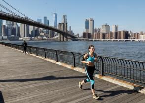 A woman runs along the East River through Brooklyn Bridge Park during unseasonably warm weather in Brooklyn, New York