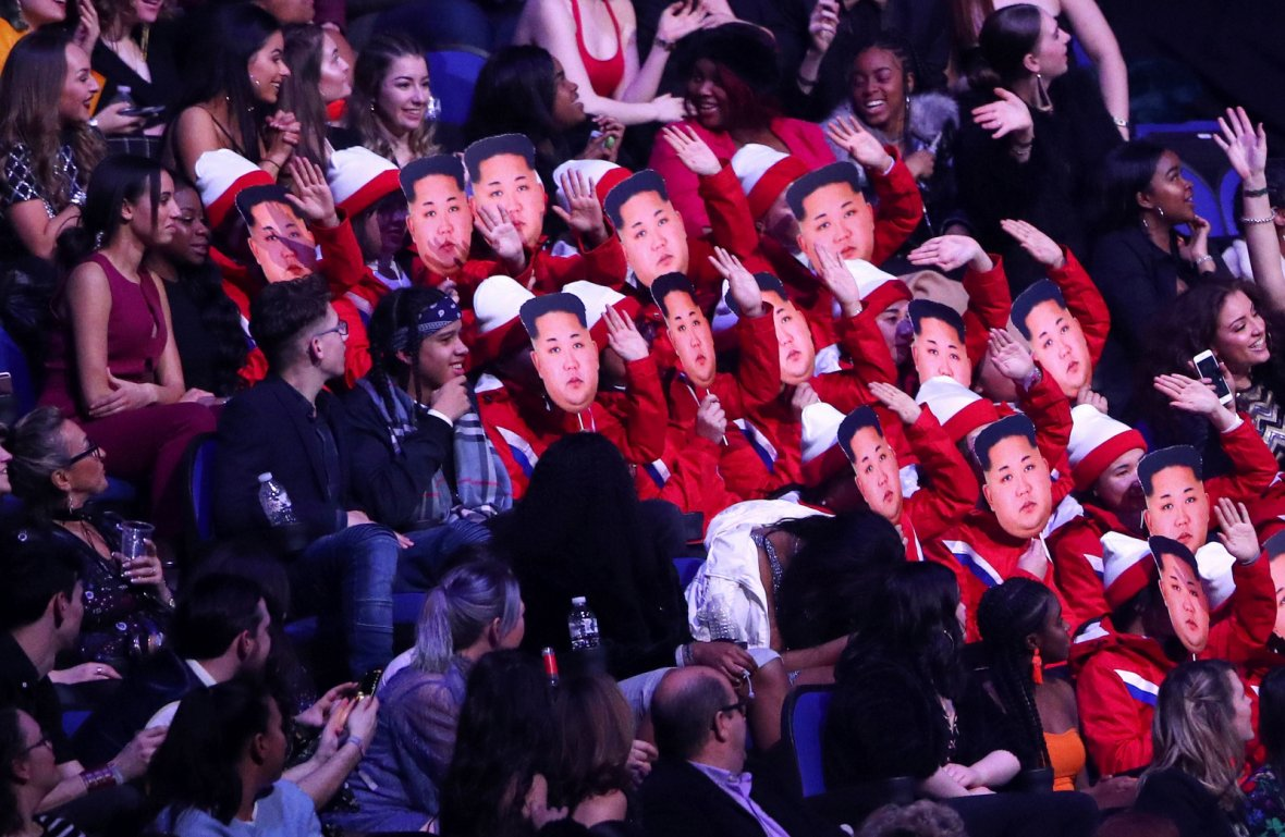 Spectators wear Kim Jong-un masks as they impersonate the North Korean cheerleaders at the Winter Olympic Games