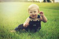 Infant sitting on the grassy ground