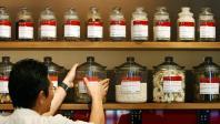 A shop assistant arranges jars containing roots and herbs at a Chinese medicine shop in Singapore