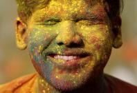 A student of Rabindra Bharati University, with his face smeared in coloured powder