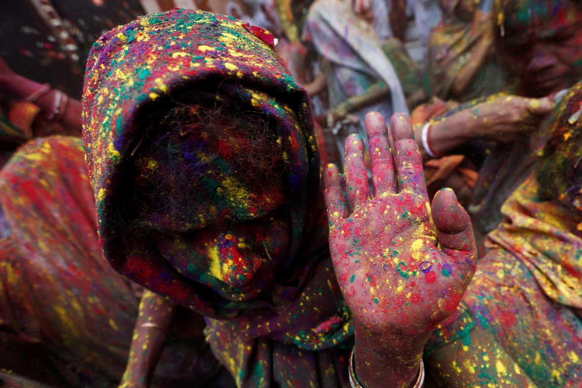 Widows daubed in colours dance as they take part in Holi celebrations
