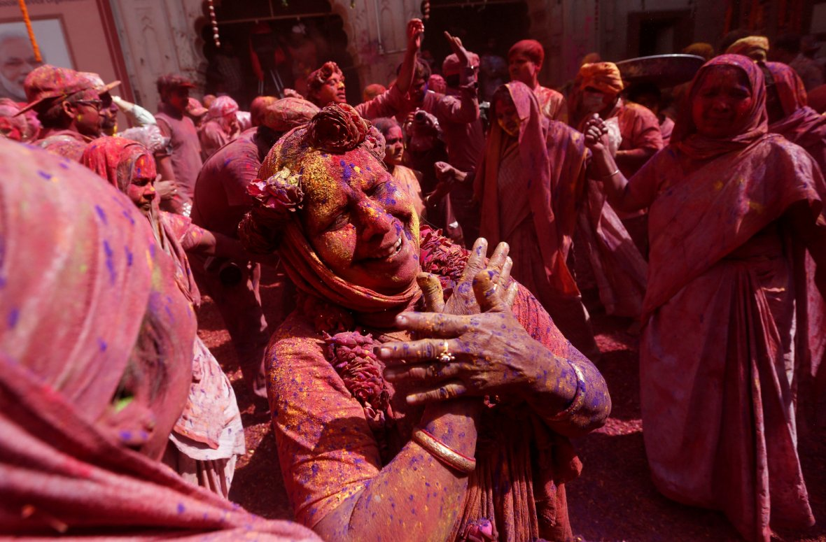 Widows daubed in colours dance as they take part in Holi celebrations in the town of Vrindavan