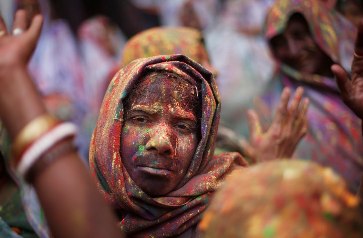 A widow daubed in colours takes part in Holi celebrations