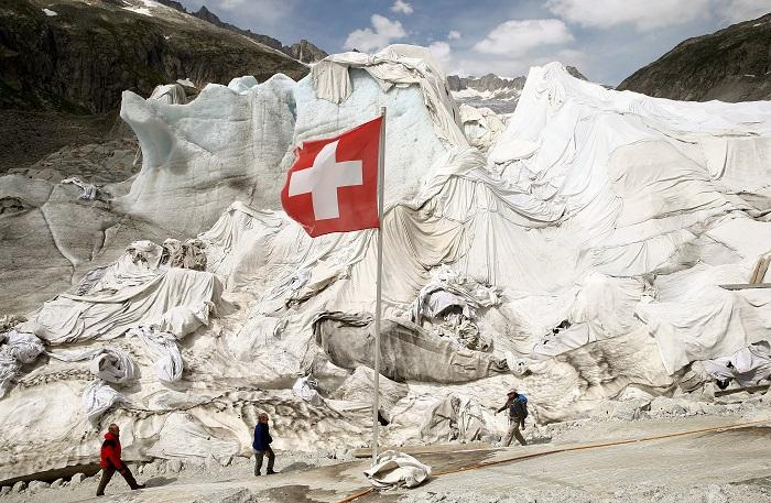 White canvas covers protect parts of the Rhone glacier against melting as visitors enter an ice cave near the Furka mountain pass