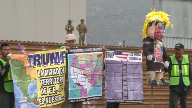 protesters-greet-president-trump-as-he-visits-border-wall-prototypes