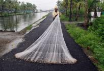 A fisherman arranges his fishing net along a road as it drizzles on the outskirts of the southern Indian city of Kochi