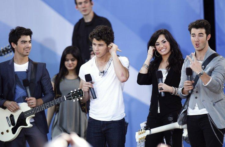 Jonas Brothers (L-R) Joe, Nick, and Kevin smile onstage with Demi Lovato