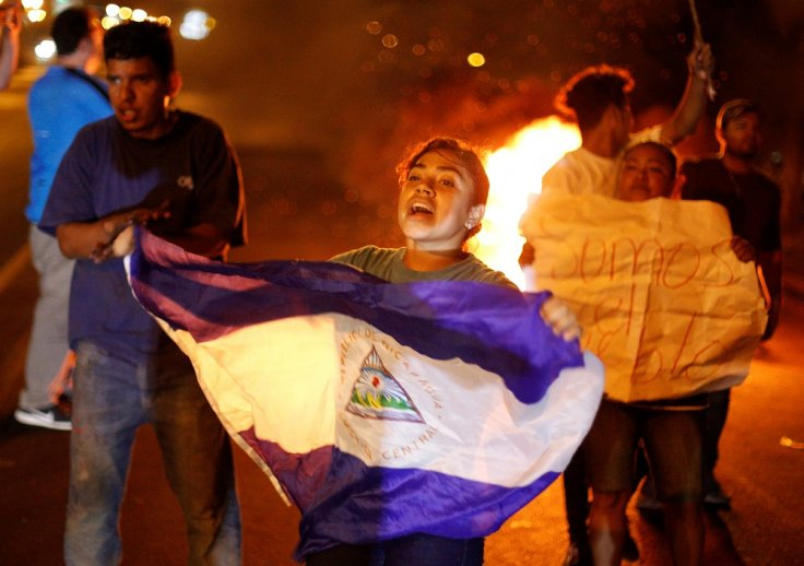 A demonstrator holds up a Nicaragua flag next to a burning barricade as demonstrators take part in a protest over a controversial reform to the pension plans of the Nicaraguan Social Security Institute (INSS) in Managua, Nicaragua April 21, 2018.
