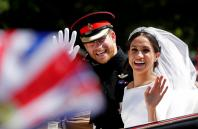 Britain's Prince Harry and his wife Meghan wave as they ride a horse-drawn carriage after their wedding ceremony at St George's Chapel in Windsor Castle in Windsor,