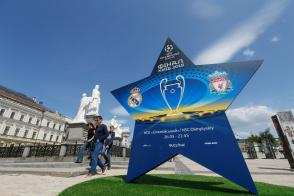 People walk pass an installation with the logo of the UEFA Champions League final in central Kiev, Ukraine
