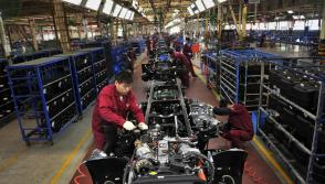 Workers install the chassis along a production line at a truck factory of Anhui Jianghuai Automobile Co. Ltd (JAC Motors) in Hefei, Anhui province