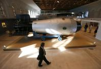 A man walks past a shell, which is the replica of the biggest detonated Soviet nuclear bomb AN-602