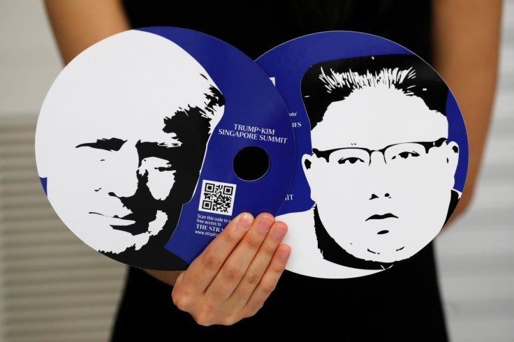 A worker of a media center for the summit between the U.S and North Korea shows fans featuring the images of U.S. President Donald Trump (L) and North Korean leader Kim Jong Un, which provided for journalists in a media kit at the media center in Singapor